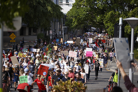 Protesters hold placards during the march. Members of the public gathered in Brisbane to protest climate change inaction. Students and workers formed a massive strike and marched from Queen's Gardens to Musgrave Park.