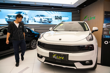 Customer looks at a Lynk & Co hybrid SUV at an electric and hybrid cars retailer in Shanghai.