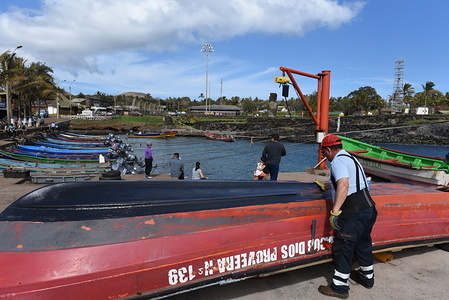A fisherman is seen painting his boat at the fishing port. Hanga Roa is the capital of Easter Island, a Chilean island in the southeastern Pacific Ocean. The village has around 5,000 inhabitants, which comprises between 87 and 90 percent of the total population of the island. Excluding a small percentage still engaged in traditional fishing and small-scale farming, the majority of the population is engaged in tourism which is the main source of income.