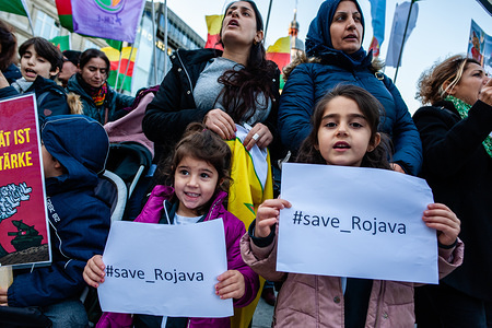 Two little girls hold placards with the hashtag save Rojava during the demonstration. Thousands of people gathered at the Cologne central station to protest against Turkey's invasion of the Kurdish-liberated democratic autonomous territories in northern and eastern Syria, popularly known as Rojava. The demonstration was surrounded by the riot police when spontaneously started to march.