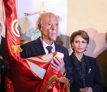 Conservative academic, Kais Saied holds the Tunisian flag as he celebrates his victory in the Tunisian presidential election after a polling agency announced that he had overwhelmingly won Tunisia's presidential run-off.