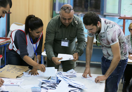 Election officials count ballots at a polling station after the second round of the presidential election.
