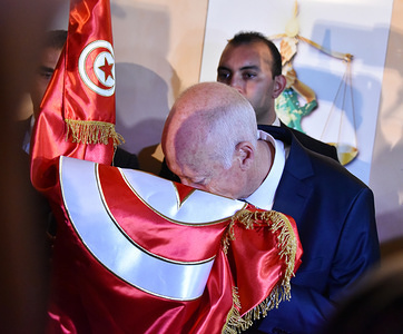 Tunisian presidential candidate Kais Saied (R) embraces the Tunisian flag during a press conference after securing more than 72% of votes in the presidential election held on Sunday said by an exit polls agency in Tunis.