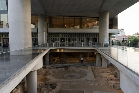 Entrance view from the Acropolis museum front forecourt. The Acropolis Museum is an archaeological museum focused on the findings of the archaeological site of the Acropolis of Athens. It has a total area of 25,000 square meters, with exhibition space of over 14,000 square meters. It hosts artefacts and findings from the Acropolis rock and the nearby area from the Greek Bronze Age to Roman and Byzantine Greece.