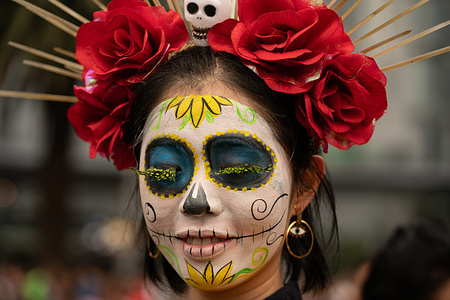 A woman with a brightly colored Catrina face paint poses for the camera during the Catrina Festival. Thousands of people took to the streets of Mexico City to watch the procession of Catrinas. Catrina is a female skeleton with a large hat, often made of feathers. The figure is based on a character created in the early 1900s by artist José Guadalupe Posada and then reinvented by Diego Rivera.