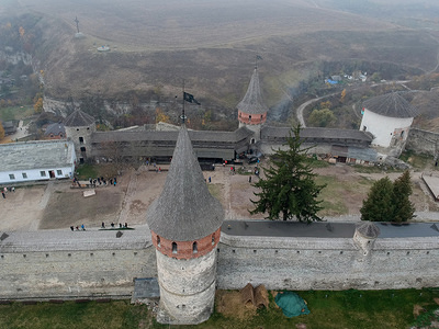 Overview of the Castle. Kamianets-Podilskyi Castle is located in the historic city of Kamianets-Podilskyi in the historic region of Podolia in the western part of the country. Its name is attributed to the root word kamin' from the Slavic word for stone. The castle is dated to the early 14th century and even earlier than this, initially built to protect the bridge connecting the city with the mainland.