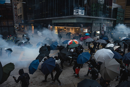 Protesters take cover behind umbrellas as tear gas rounds fly in during the demonstration. Pro-democracy protesters once again took to the streets in their latest battle against the government. Despite the full withdrawal of the extradition bill, the initial catalyst of unrest, protesters continue to reemphasize that the remaining 4 demands must be met. Protesters clashed violently with police, resulting in numerous injuries and arrests.
