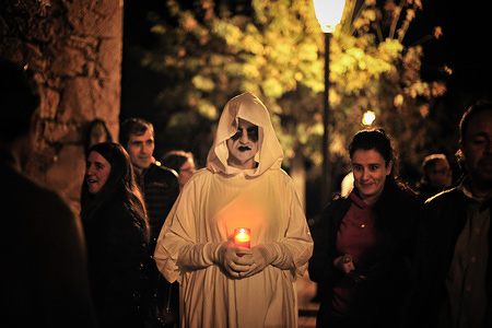 """An Almeta holds a candle during the celebration of the act of Almetas y Totones in the village of Radiquero, Huesca, Spain. All Saints Day is a tradition celebrated in the small village of Radiquero. A group of people called """"Almetas"""" dressed in white carrying candles where they represent the journey of souls on the day of all saints. They offer candles in exchange for taking the soul of the living. They walk the streets of the village ending up in the village cemetery, this year suspended due to heavy rains in the region."""