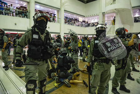 Police officers form a protective circle around their fellow officers while making arrests inside a shopping centre during clashes. Pro-democracy protesters assembled at various districts throughout Hong Kong in support of the anti-extradition movement. Large crowds attempted to gather at several malls where they faced off with heavy police forces. Protesters continue to reiterate their 5 demands despite the government's unwillingness to negotiate further.