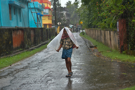 A man guarding himself from the heavy showers of rain with a plastic bag. Heavy downpours with storms is the forecast due to the very severe cyclonic storm 'Bulbul'.