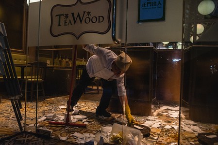 A chef cleans up the pieces of shattered dishes after protesters vandalised the restaurant during the demonstrations.  Protesters gathered at various shopping centers and malls around the city chanting slogans in support of the pro-democracy movement. Protesters later clashed with police in and around the malls as riot police attempted to conduct dispersal operations.