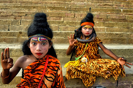 Two children dressed as Lord Shiva collecting Offerings from Devotees during the festival. Dev deepavali / Diwali is the biggest festival of light celebration in Kartik Poornima (Mid-Autumn) where devotees decorate the river bank with millions of Lamps as part of the festival.