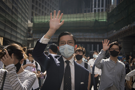 A man makes a gesture about the 5 demands during a march. Thousands of office workers and masked protesters clash with police in one of the most violent days for the financial hub since the protests began five months ago, a police officer shot a masked protester and another man was doused in fuel and set on fire. Despite the controversial extradition bill which originally sparked the protests being formally withdrawn, protesters continue to call on Chief Executive Carrie Lam to meet their remaining demands which includes complete universal suffrage, an independent investigation into police brutality, retraction of the word 'rioting' to describe the protests, and dropping all charges against arrested protesters.