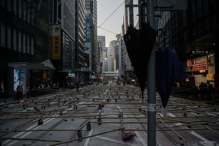 Umbrellas hang from a post in front of a road blocked using bamboo and bricks during the demonstration. Protesters called for a day of strike on the third consecutive day. Anti-government protesters blocked roads and subway accesses in the Central area of Hong Kong. A relatively calmer day after violence had returned in a response to police actions on Monday when at least two protesters were shot and many others wounded.