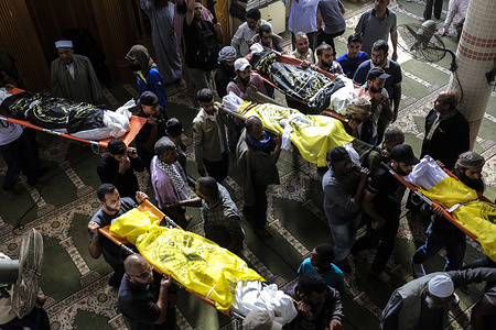 (EDITOR'S NOTE: Image depicts death) Palestinian mourners carry out the bodies of Rasmi Abu Malhous and seven members of his family during their funeral at a mosque in Deir al-Balah, central Gaza Strip. The deceased were killed in an overnight Israeli missile strike that targeted their house.