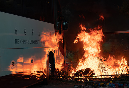A school bus being driven towards the burning barricade during the demonstrations. An unprecedented battle took place at the Chinese University Hong Kong (CUHK) as Hong Kong protests continue for the fifth month. A citywide strike called for started on 11 November, 2019 and brought parts of Hong Kong to halt as MTR stations closed and multiple roadblocks were erected.