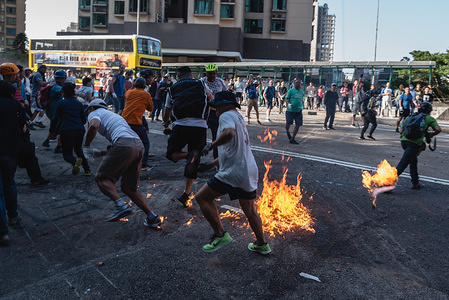 Local residents sprint away from an exploded petrol bomb hurled by protesters from a bridge during a roadblock clean up event.