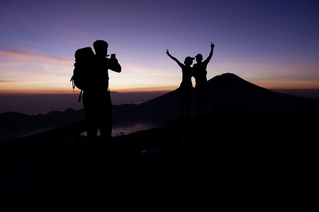 The silhouette of a group of hikers taking photos at the summit of Mount Batur in Bali during the sunrise. A popular tourist destination, Mount Batur is a 1,717 meter high active volcano located in the island of Bali in Indonesia. A two and a half hour hike up the mountain rewards visitors with breath-taking views of Lake Batur, Mount Abang and Mount Agung. The last eruption was  in 2000.