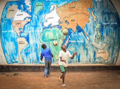 Young boys enjoy playing Soccer in front of a wall showing a map of the world and its continents. As the world comes to one of its most remarkable days (World children's day). Most children around different places of the world are seen sharing their lovely moments and togetherness. This is a moment that not many children around different parts of the word live to see or enjoy. Today in Kenya Children are seen sharing and enjoying their free world moments peacefully and forgetting the day to day struggles in Life despite everyday challenges.