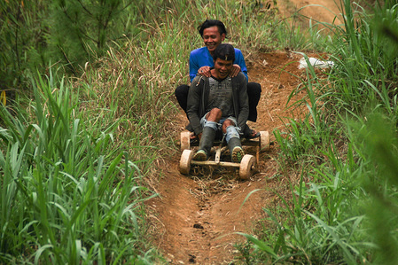 Residents glide at high speed from the top of the track on a bamboo car in Batu Lonceng Village, Lembang. The traditional game is a hereditary tradition held during the growing season holidays as well as entertainment to villagers.