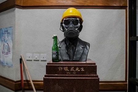 A statue at the entrance to the Hui Yeung Shing Building decorated with a construction yellow helmet, a mask and a Molotov cocktail during the demonstration. After a week of strikes and clashes with police, protesters still occupy the campus of Chinese University of Hong Kong in a day of relative calm. At the end of the day, protesters blocked again Tolo Highway in flash mob actions and then evacuated the campus helped by private drivers after setting the entrance of bridge number 2 on fire. No arrests were made.