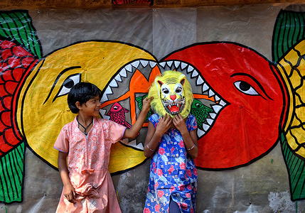 Village kids pose for a Photo with a colourful Mask next to a decorated Wall. Naya Village under Pingla Block is a small village under Paschim Midnapore District of West Bengal, India which is famous for their colourful Ancient Folk Art. Almost 60 Families of this village are associated with the Art Patachitra, an ancient folk art of Bengal, the art is appreciated by art lovers all over the world for its style of drawings, shape, pattern, textures and colours. The Art is based on mythological tales and tribal rituals to stories based on modern Indian history and contemporary issues happening in different parts of World.