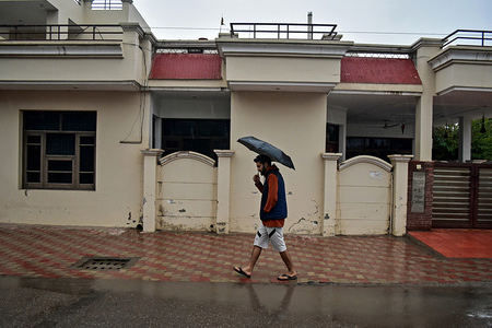 A man walks with an umbrella during heavy rainfall in Rajpura town of Patiala district.
