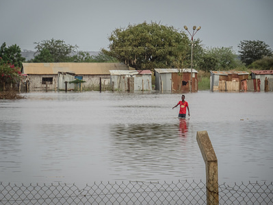 A man wades through flooded area. Businesses and homes damaged by flooding in Elegu, northern Uganda, on the border with South Sudan. Thousands of people across East Africa are currently affected by flooding.