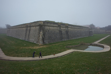 Two people walk their dog through the moat of La Cuidadela at the park of La Vuelta del Castillo amidst dense fog. Pamplona is a small town north of Spain dawned under a dense fog with a temperature of only three degrees Celsius.