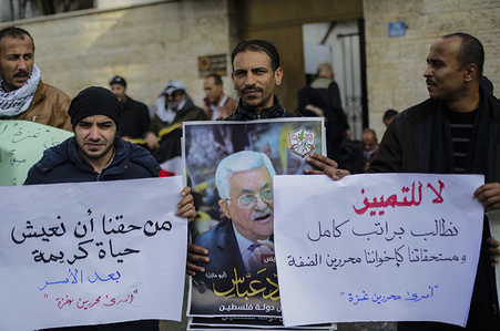 GAZA CITY, PALESTINE - DECEMBER 09 2019: Released prisoners hold posters and placards demanding for their salaries during a protest in solidarity with Palestinian detainees in Israeli jails at the Red Cross office.