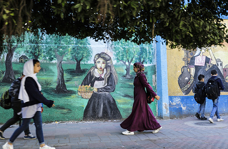Palestinians walk past a mural on the wall of the United Nations Refugee Agency (UNRWA) in Gaza City.
