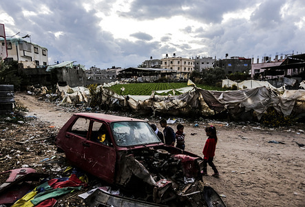 Palestinian children play close to a damaged vehicle in front of their family's tent in Beit Lahiya camp in northern Gaza Strip.