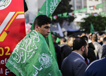 Palestinian Hamas supporter wrapped in a flag during a rally marking the 32nd anniversary of the founding of the Islamist movement Hamas.