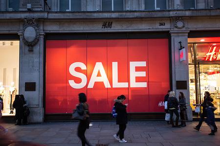 People walk past a 'sale' advertisement on Oxford Street in London.