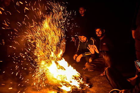 People gather around a bonfire to keep themselves warm on a cold evening in Punjab.