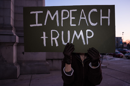 A protester holds an Impeach Trump placard during a Trump pro-impeachment rally in Dayton. The protesters gathered in Dayton to show their support for Trumps impeachment the day before the House vote.