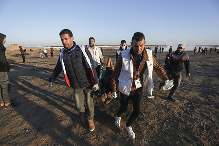 A wounded Palestinian being evacuated during the demonstration. Palestinians clash with Israeli security forces while demanding for an end to the Israeli blockade of Gaza and the right of return to their homeland at the border fence between Israel and Gaza in southern Gaza Strip.