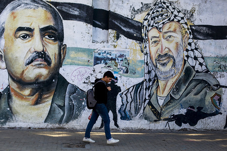 Palestinian youth walking past a mural depicting the late Palestinian leader, Yasser Arafat and the leader of the Popular Front, George Habash in Gaza City.
