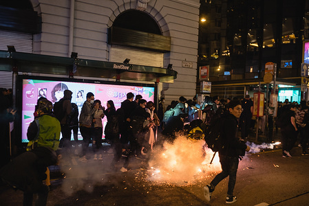 A tear gas grenade explodes in the middle of a crowd during the demonstration in Tsim Sha Tsui. Thousands of protesters gathered in support of the pro-democracy movement on Christmas Eve. Clashes between protesters soon broke out as police fired tear gas and other projectiles. Protesters also hurled various objects at the police.