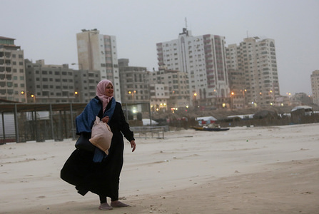 A Palestinian woman on the shores of the Sea during the strong winds in Gaza.