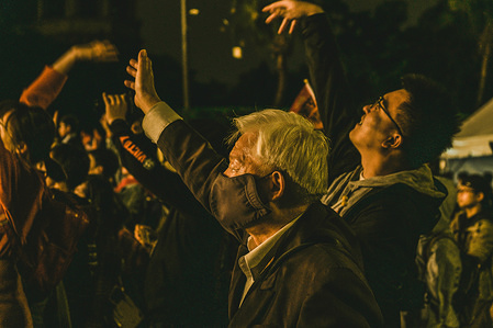 An old man cheers during the Chthonic concert and in support of Freddy Lim legislative campaign at Ketagalan Boulevard in Taipei.