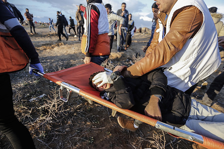 A Palestinian child who was hit by a gas bomb being evacuated during the clashes. Palestinians clash with Israeli security forces while demanding for an end to the Israeli blockade of Gaza and the right of return to their homeland at the border fence between Israel and Gaza in southern Gaza Strip.