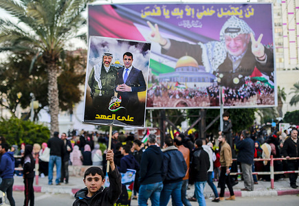 Palestinian supporters of the Fatah movement hold placards during a rally marking the 55th anniversary of Fatah movement, a secular Palestinian political party and former guerrilla movement founded by Yasser Arafat, in Gaza City.