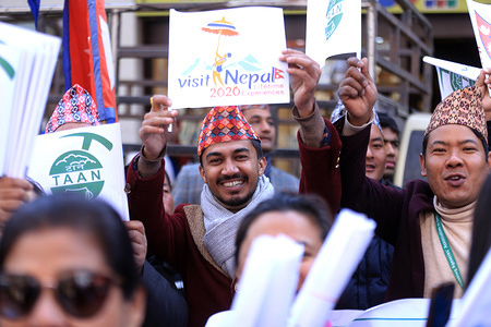 Nepali nationals smile with a placard during the campaign. Nepali nationals participate in a campaign in Kathmandu aimed at boosting local and international tourism in Nepal dubbed 'Visit Nepal 2020' that was organised by the government.