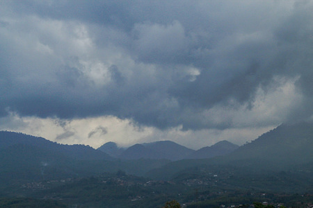 Black clouds cover the hilly area in Tanjungsari, Sumedang Regency.