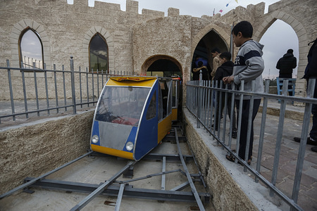 "A kid looks at the moving train during the opening. Palestinians open up an amusement suspension railway dubbed ""The Return Train"" at the theme park in Khan Yunis."