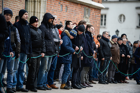 """Participants pray during the monthly Men's Rosary at the Main Square in Krakow. Few dozens of Catholic Polish men gather every first Saturday of the month to pray and """"participate in a spiritual battle"""" begging forgiveness for blasphemy."""