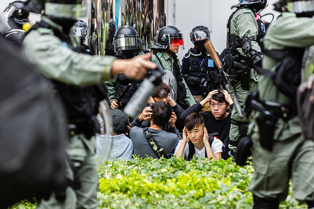 Police in riot gear rounding up suspected protesters during the demonstration. Entering the 7th month of civil unrest, protesters marched the streets, protesting against Chinese parallel traders. Demonstrators chanted slogans and sang songs. Police in riot gear appeared and arrested several protesters.