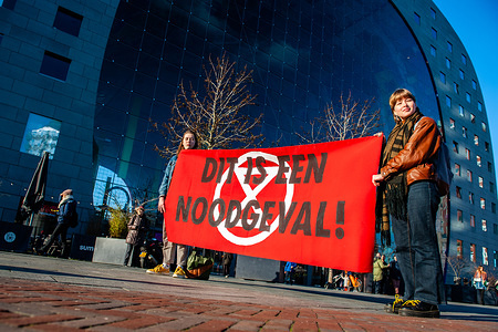 Extinction rebellion activists hold a  banner during the rally. All over the Netherlands, the public warning sirens are tested at exactly 12.00 noon on the first Monday of every month. For the second time, in Rotterdam during the air alarm, a 'die-in' action was carried out by XR Nederland at several places in the Netherlands to emphasize that the climate crisis is not a drill, but an actual emergency. With this action, XR Rotterdam wanted to draw attention to the ecological crisis in general and the sea level threat in particular. With theatrical means, the group displayed an emergency situation by using life jackets, crisis blankets followed by a speech. This time the action took place in Markthal, and more activists were present to recreate a state of emergency.