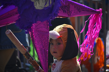 A child seen behind a Piñata during the Epiphany Day celebration. This year the Mexico City Government organised a feast with kings thread pastries, toys and a thousand piñatas for the kids.